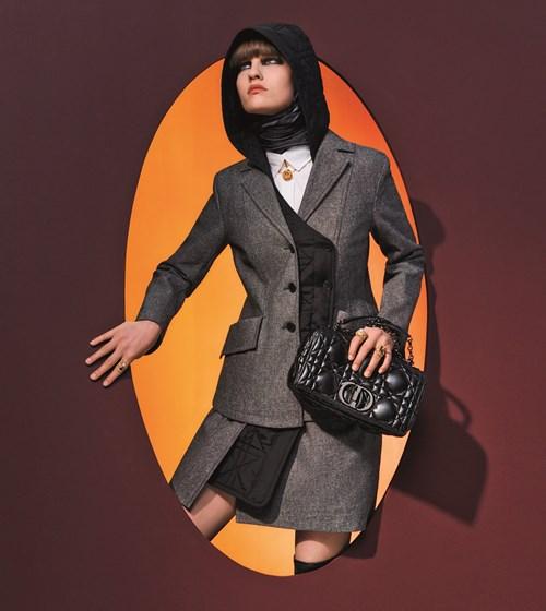 وشاح من الحرير الأسود. عقد وخواتم. جاكيت أسود ورمادي. قميص أبيض. تنورة رمادية. وحقيبة «Dior Caro» سوداء.